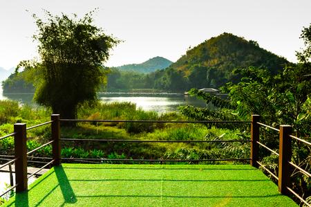 houten zonnebank op groen kunstgras en kijken naar de blauwe hemelachtergrond Stockfoto