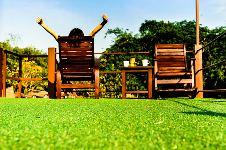 woman relaxing on wooden sunbed on green artificial grass and looking the blue sky background Stockfoto