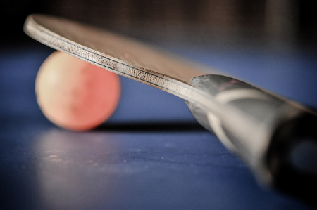 table tennis racket with orange ball on blue table