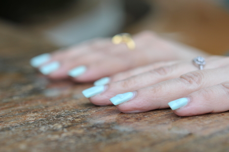 Hand gestures of a fat caucasian woman with beautiful nails polish and ring on the wooden table
