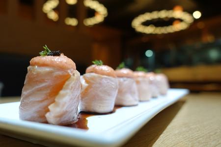Gros plan de rouleaux de saumon disposés sur une assiette blanche avec un beau plat d'accompagnement, élégant, sur la table du restaurant. Arrière-plan flou derrière dans le restaurant. Banque d'images