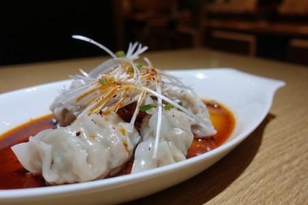 Close up fresh boiled gyoza dumplings with hot steams, Asian dumplings Gyozas potstickers fried over black plate, cooking gyoza dumplings, potstickers, Japanese food.