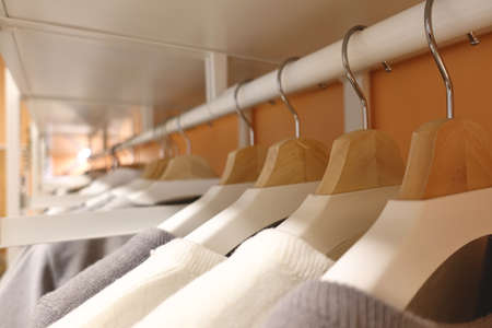 modern wooden wardrobe with clothes hanging on rail in walk in closet, Choice of fashion clothes of different colors on wooden hangers