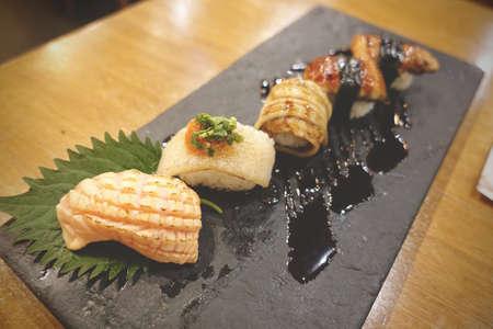 Sushi rolls set served on gray stone slate on metal background 写真素材