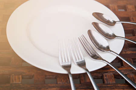 spoon and fork in white plate on wooden table