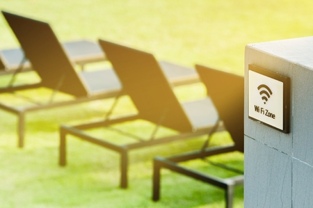 Wireless internet sign on the wall near with sun bed on the grass field, relaxing and working business area