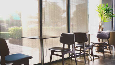 interior of restaurant cafe with window glass with window blinds and table with chair against green color of tree