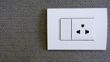 White Electrical Outlet and Wall Plate at the decoration wallpaper grey color on the wall.