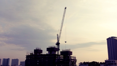 Silhouette construction crane and construction site at Thailand in sunset time.