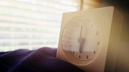 old memory time concept, retro square clock timed at 6 oclock on the bed with sun light from window