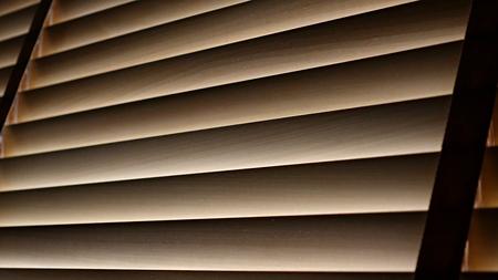 Evening sun light outside wooden window blinds, blind background