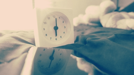 Alarm clock (6 o clock in the morning) on the bed at home. Morning time background concept, soft focusing and vintage color style.
