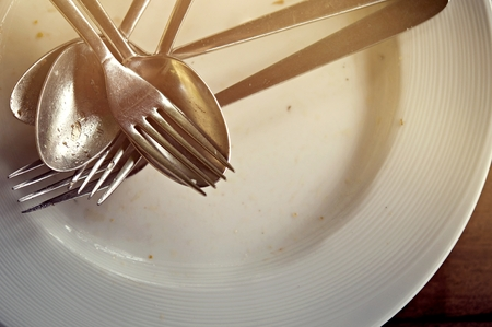 empty and dirty dish with fork and spoon on the wooden table after eating in the restaurant. The concept of mess, dirty dishes. not good for health. Imagens