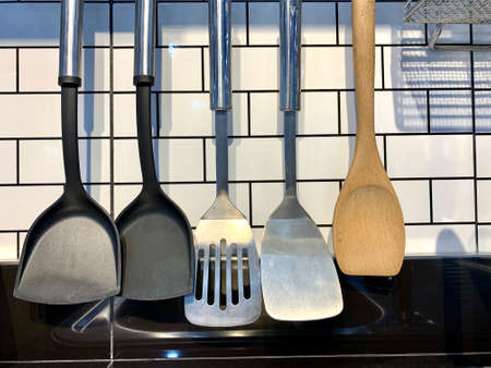 any type of spatulas Hanging metallic stainless kitchenware utensils (spatulas or spoons) above a stove cooker from a professional restaurant white wall background. 写真素材