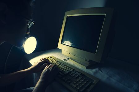 A man using an old personal computer and monitor . Ancient concept