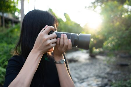 Asian woman photographer in nature. Taking pictures right side