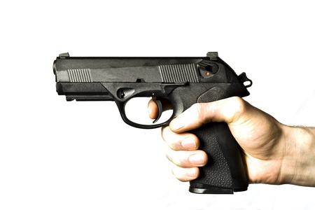 Man firing a .45 caliber pistol.  The mans hand is pulling the trigger and the hammer is cocked.  The pistol is isolated on white.