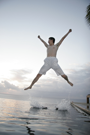 Young man jumping spreadeagled Imagens