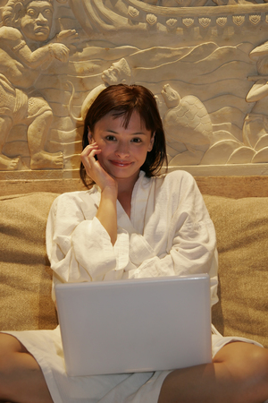 Young woman sitting with computer on legs