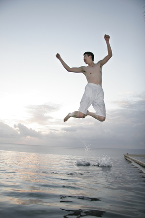 Young man jumping from water