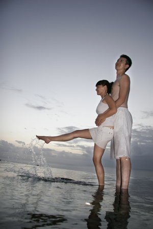Young couple embrace at the edge of water
