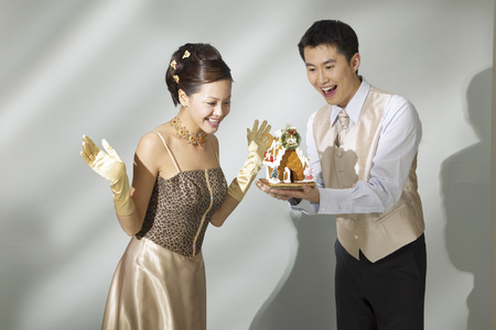 Young man showing toy house to young woman Stock Photo
