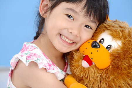 Little girl holding a plush lion