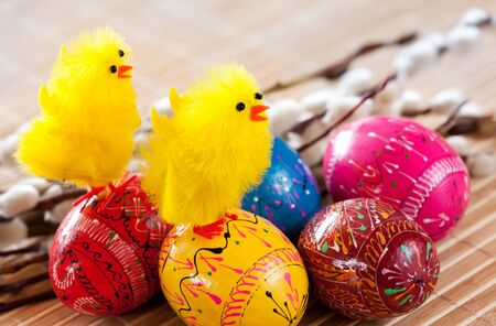 Easter eggs and yellow fluffy chickens Stock Photo
