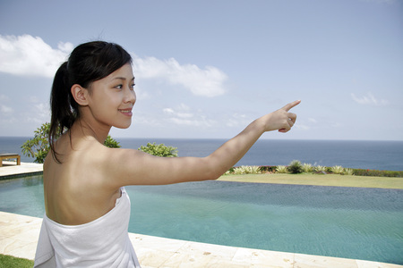woman in bath: Young woman pointing to the sea Stock Photo