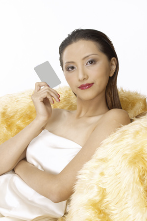 Portrait of young woman holding credit card