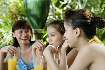 Three young women drinking juice