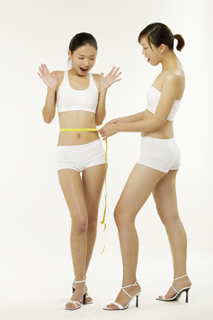 Young woman measuring waistline Stok Fotoğraf - 80672540