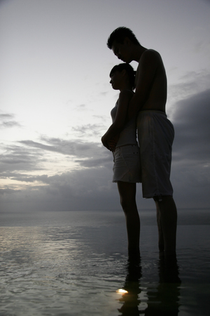 Intimate Couple Embrace at the edge of water Stock Photo