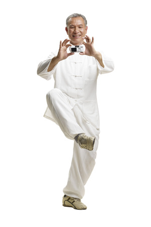 Portrait of senior man wearing Tai Chi clothes holding a camera in hand