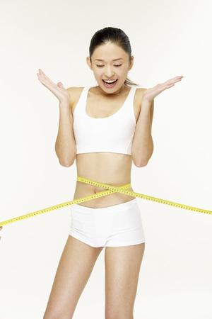 Young woman measuring waistline Stok Fotoğraf - 80767245