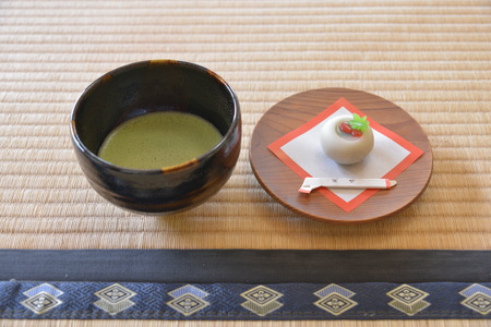 Close up view of a cup of matcha and a plate of dessert Editorial
