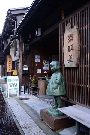 Exterior view of a shop in Japan with a sculpture at the outside Editorial