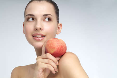 smiled: Close-up of young woman holding an apple LANG_EVOIMAGES