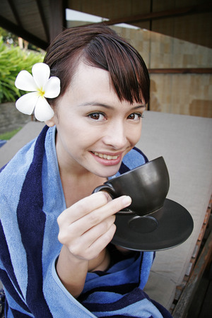oriental bathrobe: Young woman drinking tea LANG_EVOIMAGES