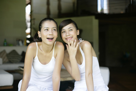 smiled: Two young women sitting together LANG_EVOIMAGES