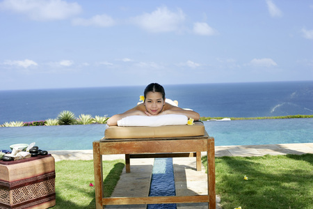 smiled: Womon lying on massage table outdoors