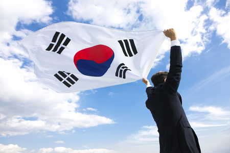 high winds: Portrait of businessman with national flag