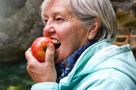 Healthy looking senior woman with grey hair eating apple outside in the park