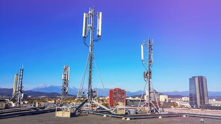 Antena de red celular que irradia y difunde fuertes ondas de señal de potencia sobre la ciudad en el techo de un edificio con mástil de telecomunicaciones
