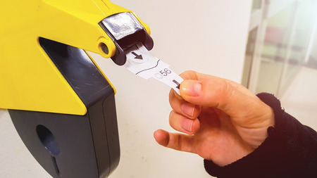 Customer pulls with hand a numbered ticket out of yellow number dispenser machine, to wait in service line and to be served when his number is displayed Stockfoto