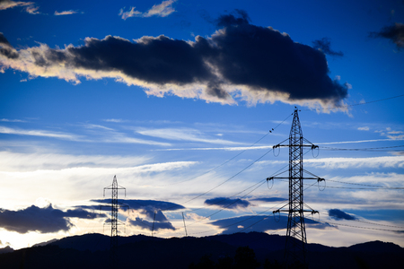 Big black clouds over the hi voltage power grid line infrastructure with sun set in the background