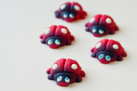 Group of red ladybugs with blue eyes