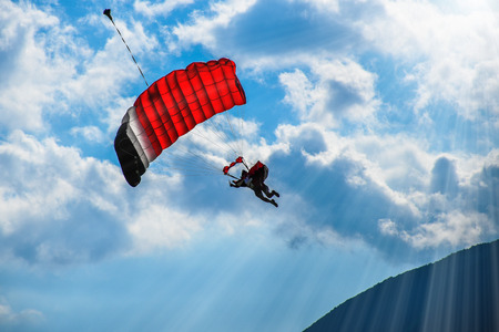 Paraglider with red parachute flying in the blue sky with white clouds on a sunny day