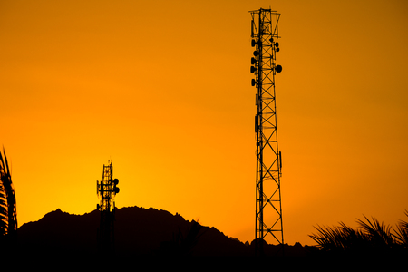 Silhouette of telecommunication antenna cellular tower for telephony with beautiful sunset Banco de Imagens