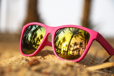 Pink modern sunglasses on the beach sand with palm trees and sunset Reklamní fotografie